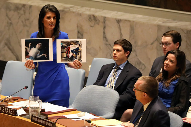 US ambassador to the UN Nikki Haley holds photographs of victims during a meeting at the UN Security Council on Syria at the UN headquarters in New York City, NY, US April 5, 2017. Credit: Reuters