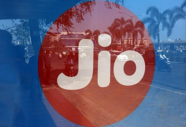 Commuters are reflected on an advertisement of Reliance Industries' Jio telecoms unit, at a bus stop in Mumbai, India, February 21, 2017. Credit: Reuters