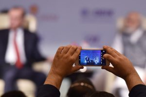 A delegate clicks a picture of Prime Minister Narendra Modi and Turkish President Recep Tayyip Erdogan at the India-Turkey Business Summit in New Delhi on Monday. Credit: PTI/Manvender Vashist