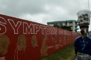 A resident walks past a mural about the dangers of the Ebola Virus painted on a wall off Tubman Boulevard in Monrovia, Liberia, on September 18, 2014: Credit: Morgana Wingard/UNDP