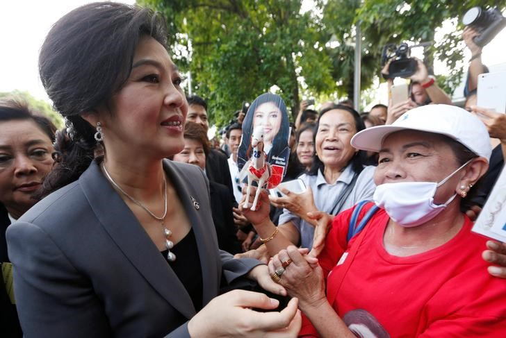 Ousted former Thai Prime Minister Yingluck Shinawatra greets supporters as she arrives at the Supreme Court for a trial on criminal negligence, which looks into her role in a debt-ridden rice subsidy scheme during her administration, in Bangkok, Thailand July 7, 2017. REUTERS/Chaiwat Subprasom