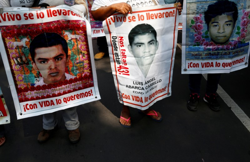 Relatives hold posters with images of some of the 43 missing students of Ayotzinapa College Raul Isidro Burgos as they take part in a march to mark National Teachers' Day along Reforma avenue, in Mexico City, Mexico May 15, 2017. Credit: Reuters/Henry Romero/File Photo