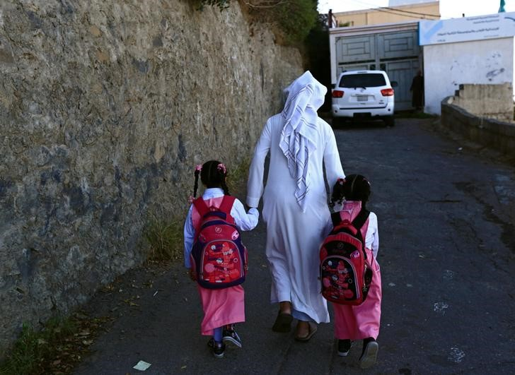 Saudi man Yazid al-Fefi holds the hands of his daughters as they arrive to their school after making their way through Fifa Mountain, in Jazan, south of Saudi Arabia, December 15, 2016. Picture take December 15, 2016. Credit: Reuters/Mohamed Al Hwaity