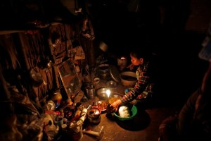 A woman cooks dinner by candlelight in her home in Dala township, outside Yangon, Myanmar, February 6, 2017. Credit: Reuters/Soe Zeya Tun
