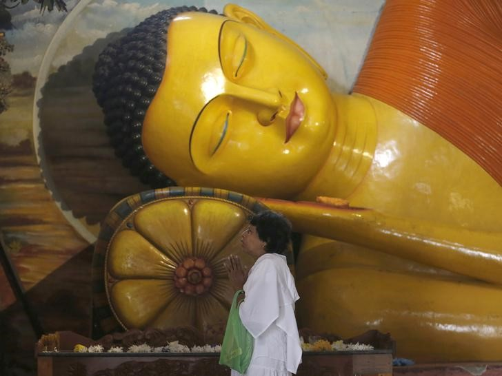 A Buddhist devotee worships in front of a Buddha statue at a temple during Poson Poya day in Colombo June 2, 2015. Credit: Reuters/Dinuka Liyanawatte