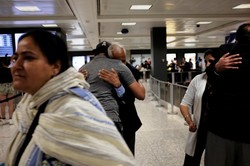 International passengers embrace family members as they arrive at Washington Dulles International Airport after the Trump administration's travel ban was allowed back into effect pending further judicial review, in Dulles, Virginia, US, June 29, 2017. Credit: Reuters/James Lawler Duggan