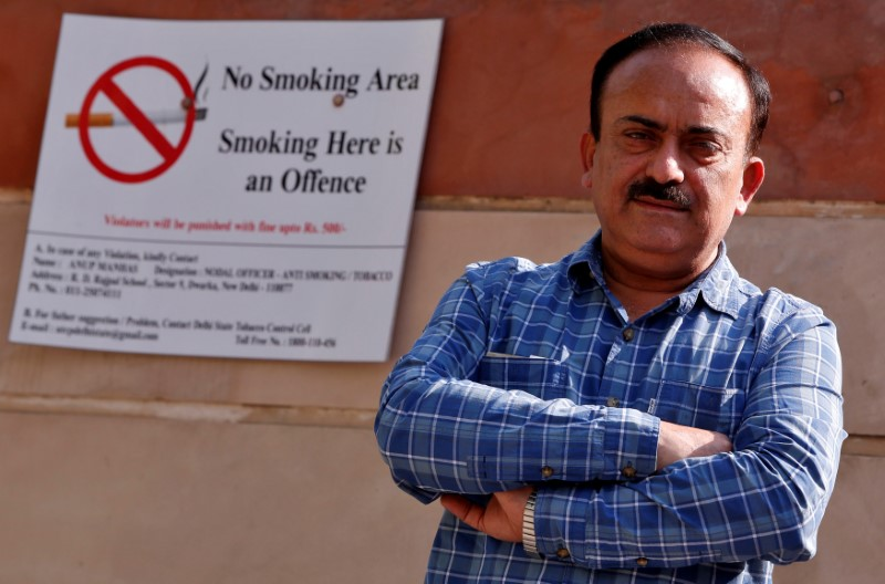 S.K. Arora, chief tobacco control officer of Delhi's state government, poses for a photograph next to an anti-tobacco sign pasted on a school wall alongside a road in New Delhi, India, April 13, 2017. Credit: Reuters/Adnan Abidi