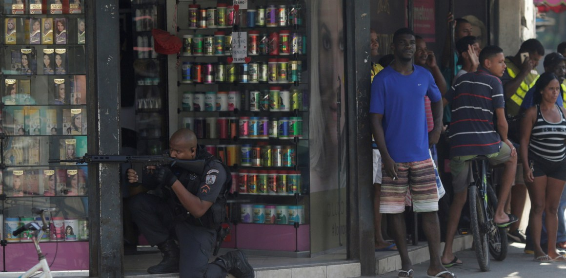 Residents react as a policeman takes up position during an operation against drug dealers in Cidade de Deus slum in Rio de Janeiro, Brazil, June 12, 2017. Credit: Reuters/Ricardo Moraes