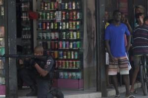 Residents react as a policeman takes up position during an operation against drug dealers in Cidade de Deus slum in Rio de Janeiro, Brazil, June 12, 2017. Credit: Reuters/Ricardo Moraes