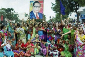 Women members of Dalit Community carry a portrait of BR Ambedkar as they block the traffic during a protest in Ahmedabad on Wednesday against the assault on dalit members by cow protectors in Rajkot district, Gujarat. Credit: PTI