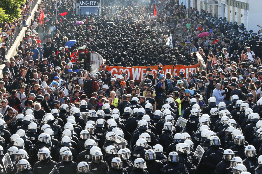 German riot police stand in front of protesters during demonstrations. Credit: Reuters
