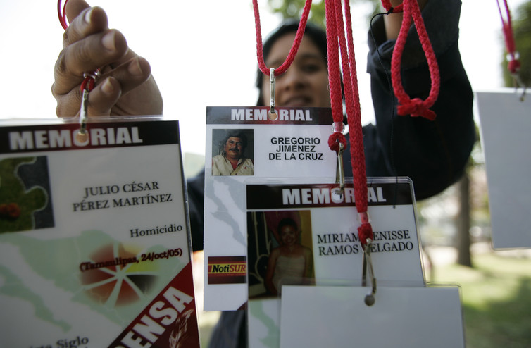 A woman hangs media accreditations with the names of journalists killed while covering the news in Mexico. Credit: Reuters