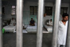 File photo of inmates resting behind bars in a barrack at Kotbhalwal central jail in Jammu, May 18, 2011. Credit: Reuters/Mukesh Gupta