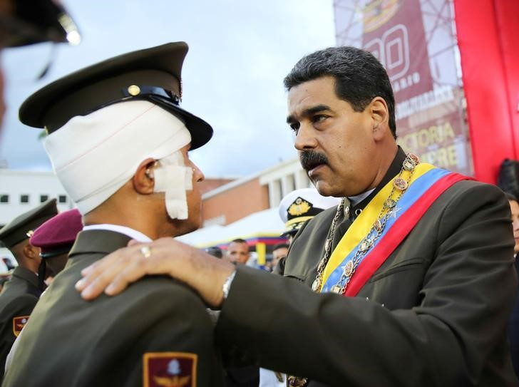 Venezuela's President Nicolas Maduro (R) decorates an injured Venezuela's National Guard during a military parade to celebrate the 80th anniversary of the Venezuela's National Guard, in Caracas, Venezuela, August 4, 2017. Credit: Miraflores Palace/Handout via Reuters