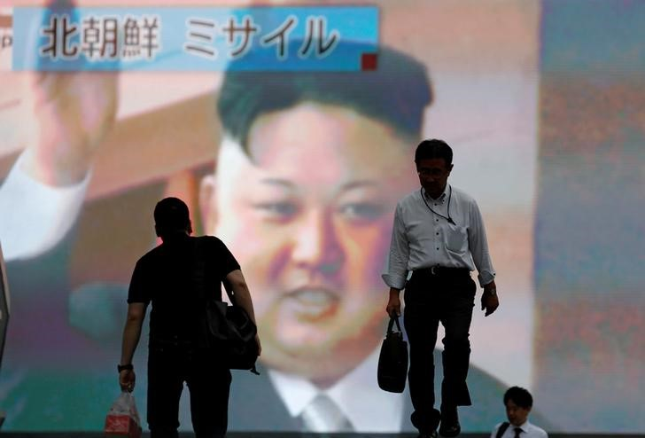 Men walk past a street monitor showing news of North Korea firing a ballistic missile, in Tokyo, Japan, July 4, 2017. Credit: Reuters/Toru Hanai/Files