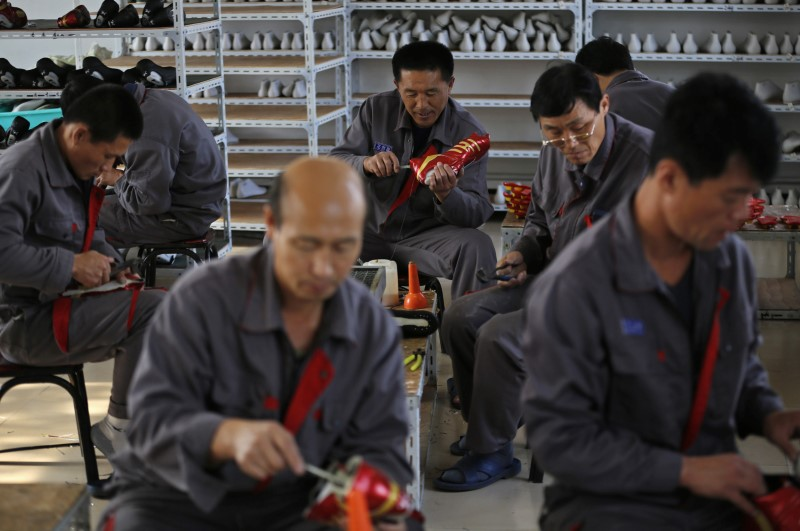 FILE PHOTO - North Korean workers make soccer shoes inside a temporary factory at a rural village on the edge of Dandong, Liaoning province, China, October 24, 2012. Credit: Reuters/Aly Song/File Photo