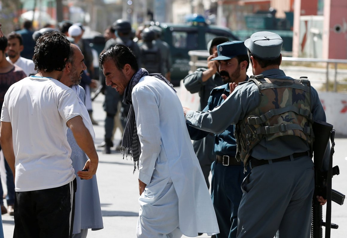 Afghan policemen try to comfort a man whose relatives were stuck at the site of a suicide attack followed by a clash between Afghan forces and insurgents after an attack on a Shi'ite Muslim mosque in Kabul, Afghanistan, August 25, 2017. Credit: Reuters/Omar Sobhani