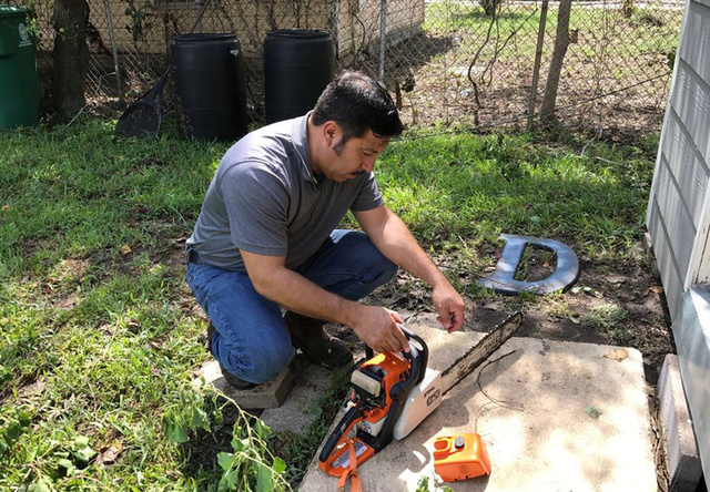Jay De Leon, of Houston, Texas adjusts his chain saw as he works in his backyard in Houston, Texas, U.S., August 30, 2017. Credit:Reuters