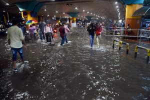 Commuters walk through flooded streets after heavy rains at Thane in Mumbai on Tuesday. Credit: PTI