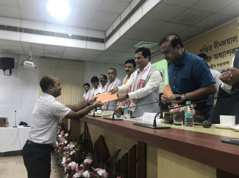 Assam chief minister Sarbananda Sonowal distributing appointment letters to teachers for the colleges named after Deendayal Upadhaya in Guwahati. State education minister Himanta Biswa Sarma seen on the right. Credit: Twitter