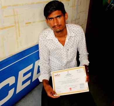 Rakesh holding the Unarmed Security Guard training certificate under PMKVY in Kalwar village. Credit: Shruti Jain