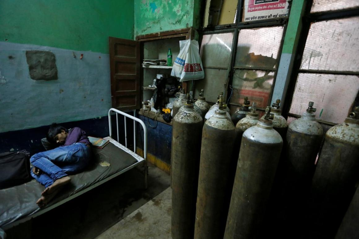 A man sleeps in a room containing oxygen tanks in the Baba Raghav Das hospital in Gorakhpur. Credit: Reuters/Cathal McNaughton