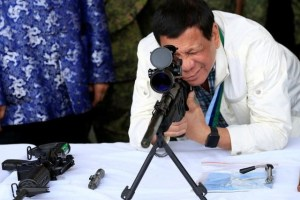 "Philippine President Rodrigo Duterte checks the scope of a 7.62mm sniper rifle during the turnover ceremony of China's urgent military assistance given ""gratis"" to the Philippines, at Clark Air Base, near Angeles City, Philippines June 28, 2017. (Reuters)"
