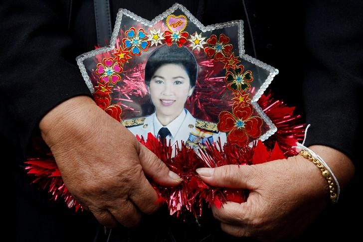 A supporter of ousted former Thai Prime Minister Yingluck Shinawatra holds a picture of Yingluck while waiting for former PM Yingluck's arrival at the Supreme Court in Bangkok, Thailand June 29, 2017. Credit: Reuters/Chaiwat Subprasom/File Photo