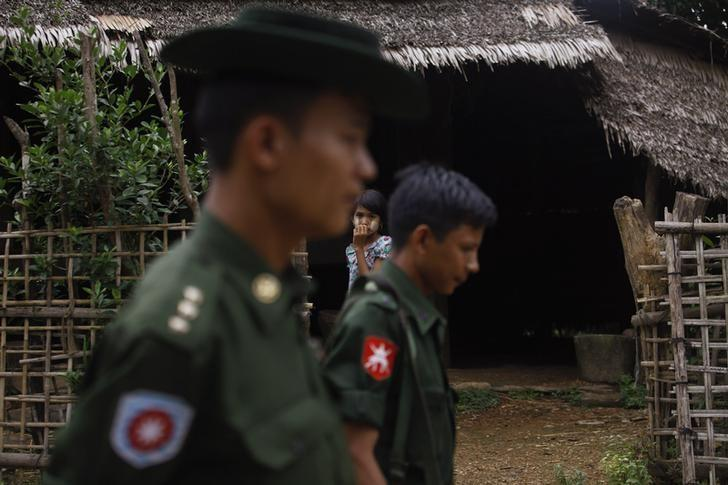 A Muslim girl watches from the doorway of her home as soldiers walk by in Thapyuchai village, outside of Thandwe in the Rakhine state, October 2, 2013. Credit: Reuters/Soe Zeya Tun/Files