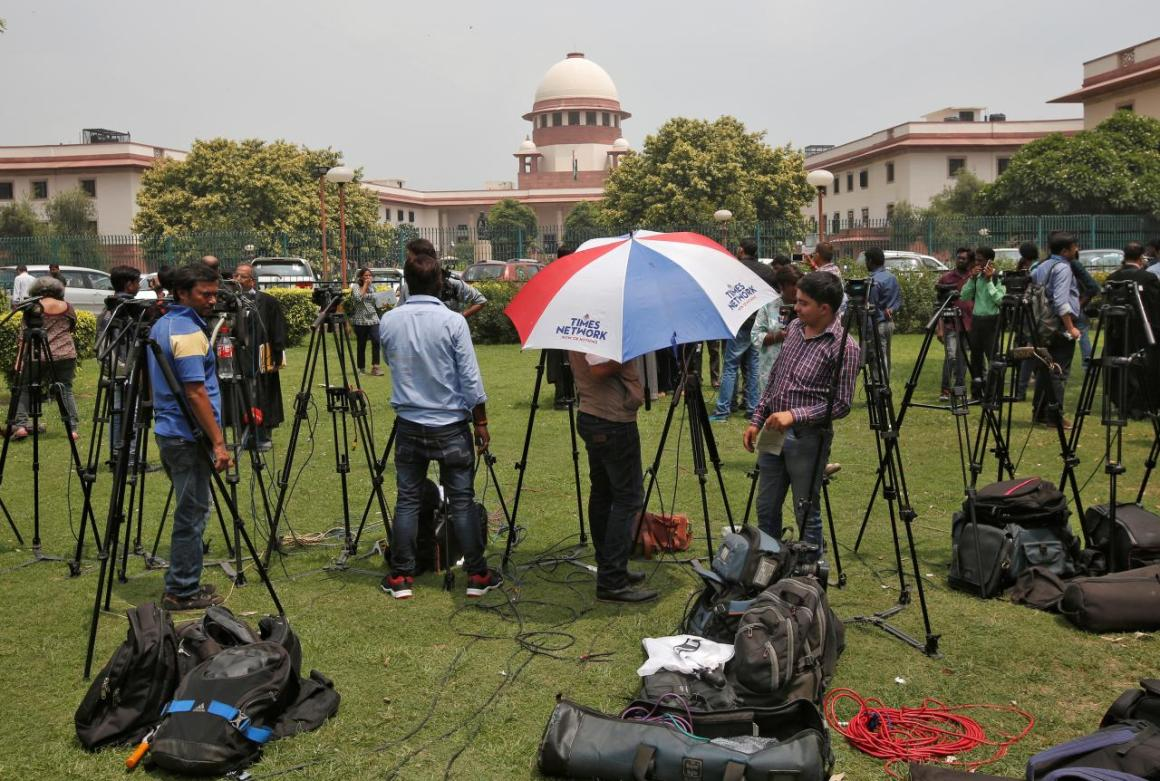 Television journalists are seen outside the premises of the Supreme Court in New Delhi, India August 22, 2017. Credit: Reuters/Adnan Abidi
