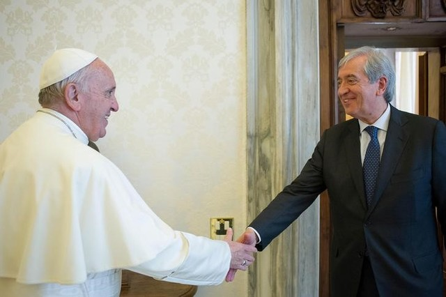 Pope Francis is greeted by Libero Milone (R), the Vatican's auditor general, during a meeting at the Vatican