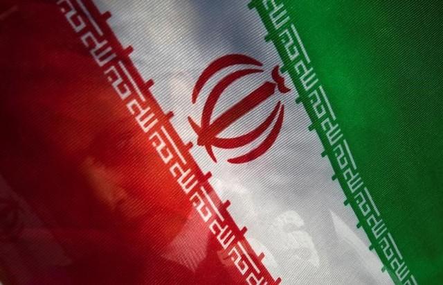 A young boy stands behind an Iranian flag at Tehran's Mehrabad International Airport, Iran, May, 5, 2010. Credit:Reuters