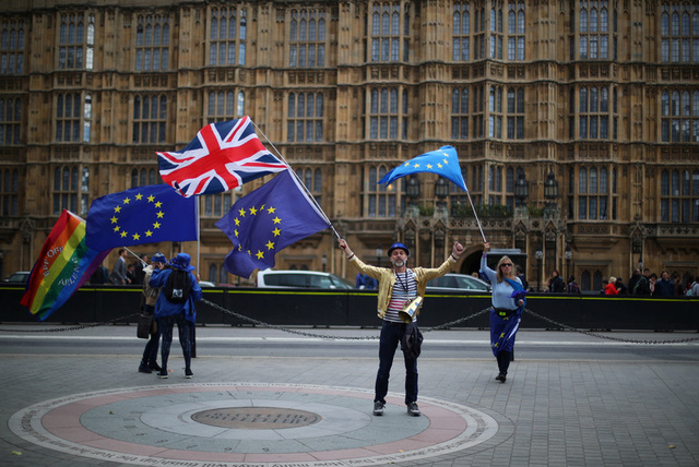 Anti-Brexit protesters wave flags in front of the Houses of Parliament in London, Britain, September 11, 2017. Credit: Reuters