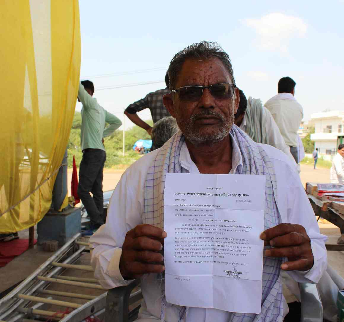 Sevaram holding up the notice from the magistrate regarding the auction of his property. Credit: Shruti Jain
