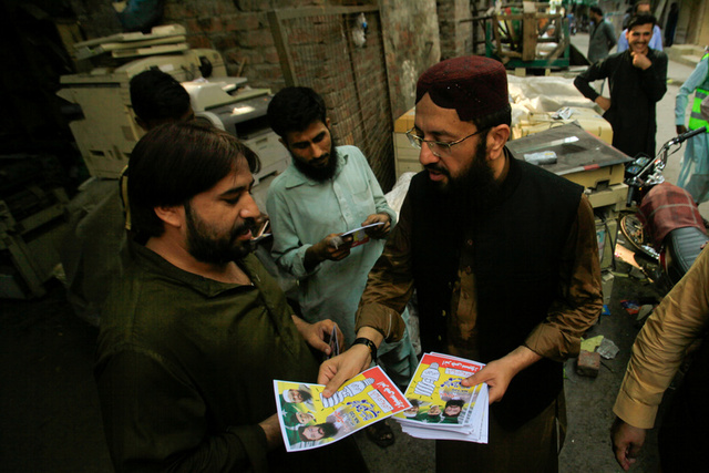 Mohammad Yaqoob Sheikh (R) nominated candidate of political party, Milli Muslim League (MML), distributes handbills to residents during an election campaign for the National Assembly NA-120 constituency in Lahore, Pakistan September 10, 2017. Picture taken September 10, 2017. Credit: Reuters