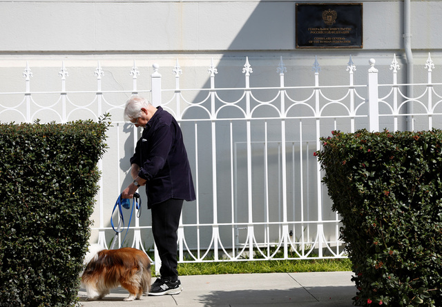 A man walks his dog outside the gate to the entrance of the Consulate General of Russia in San Francisco, California, U.S., August 31, 2017. Credit:Reuters