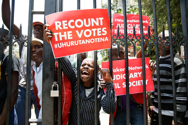 Supporters of Kenya's President Uhuru Kenyatta carry placards as they demonstrate outside the Supreme Court in protest of the nullification of Kenyatta's victory by the Supreme Court Judges in Nairobi, Kenya, September 19, 2017. Credit: Reuters