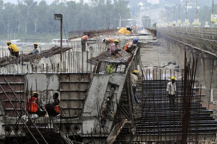 Labourers work at the construction site of a highway bridge on the outskirts of Jammu August 31, 2013. Credit: Reuters/Mukesh Gupta/Files