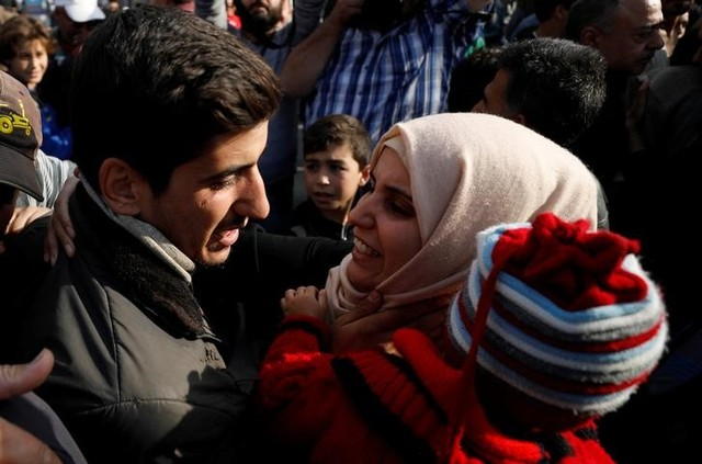 A relative reacts as she stands next to one of the hostages who escaped from his Islamic State captors in Qaryatayn town in Homs province, Syria October 29, 2017. Credit: Reuters/Omar Sanadiki