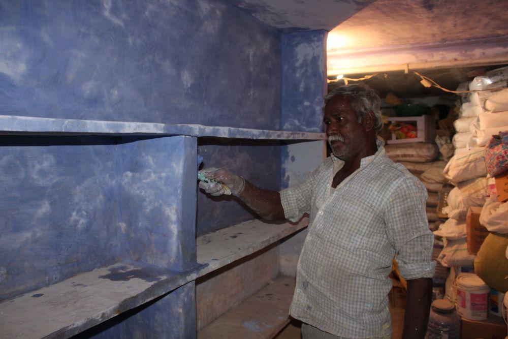 Laxmi Narayan painting his own shop in Kishanpole Bazar. Credit: Shruti Jain