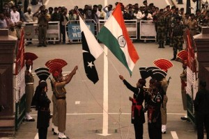 Pakistani rangers (wearing black uniforms) and Indian Border Security Force (BSF) officers lower their national flags during a daily parade at the Pakistan-India joint check-post at Wagah border, near Lahore November 3, 2014. Credit: Reuters/Mohsin Raza/Files