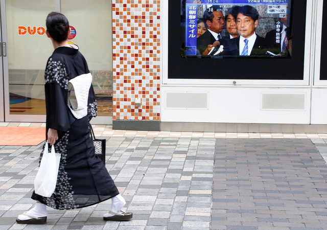 A woman in Kimono watches a TV set showing Japan's Defense Minister Itsunori Onodera in a news report about North Korea's missile launch in Tokyo, Japan, August 29, 2017. Credit: Reuters