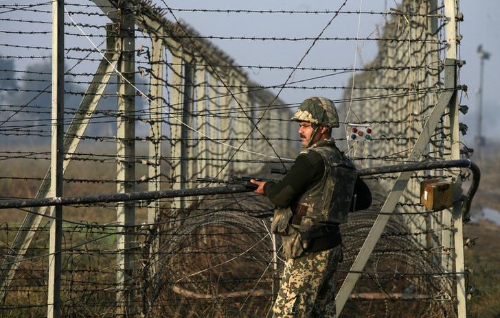 An Indian Border Security Force (BSF) soldier patrols near the fenced border with Pakistan in Suchetgarh, southwest of Jammu January 11, 2013. Credit: Reuters