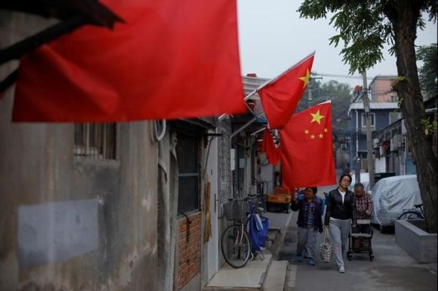 A hutong alley is decorated with Chinese national flags in an old part of Beijing as the capital prepares for the 19th National Congress of the Communist Party of China, October 15, 2017. Credit: Reuters