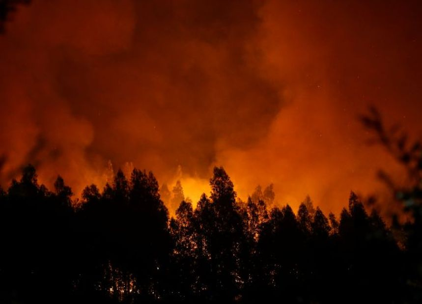 Smoke and flames from a forest fire are seen near Lousa, Portugal, October 16, 2017. Credit: Reuters