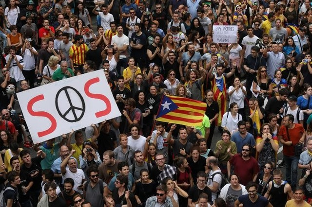 People hold up placards during a demonstration two days after the banned independence referendum in Barcelona, Spain Credit: Reuters