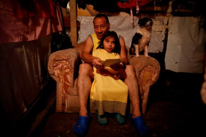 Rafael Hernandez, 62, who lost his home in the 1985 earthquake, looks at pictures with his granddaughter in his house at the camp known as No.3 in Mexico City, Mexico, September 27, 2017. The camp was founded in 1985 after an earthquake, which killed around 5,000 people. Credit: Reuters