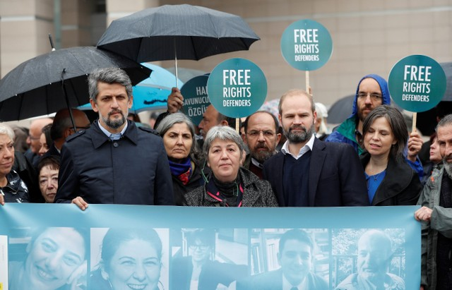 Rights activists gather in front of the Justice Palace during the opening hearing of the trial of eleven human rights activists accused of terrorism charges, in Istanbul, Turkey, Credit: Reuters