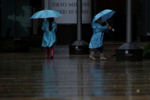Children wearing rain suits walk in a heavy rain as Typhoon Lan approaches Japan's mainland, in Tokyo, Japan, October 22, 2017. Credit: Reuters