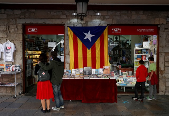 People browse at a bookshop adorned with a large Catalan separatist flag the day after the Catalan regional parliament declared independence from Spain in Girona, Spain, October 28, 2017. Credit: Reuters/Rafael Marchante